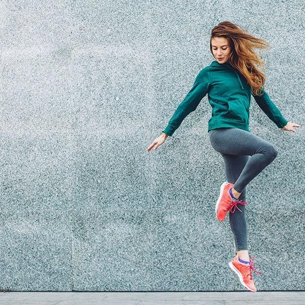 Ragazza salta felice dopo una sessione di allenamento per dimagrire le gambe