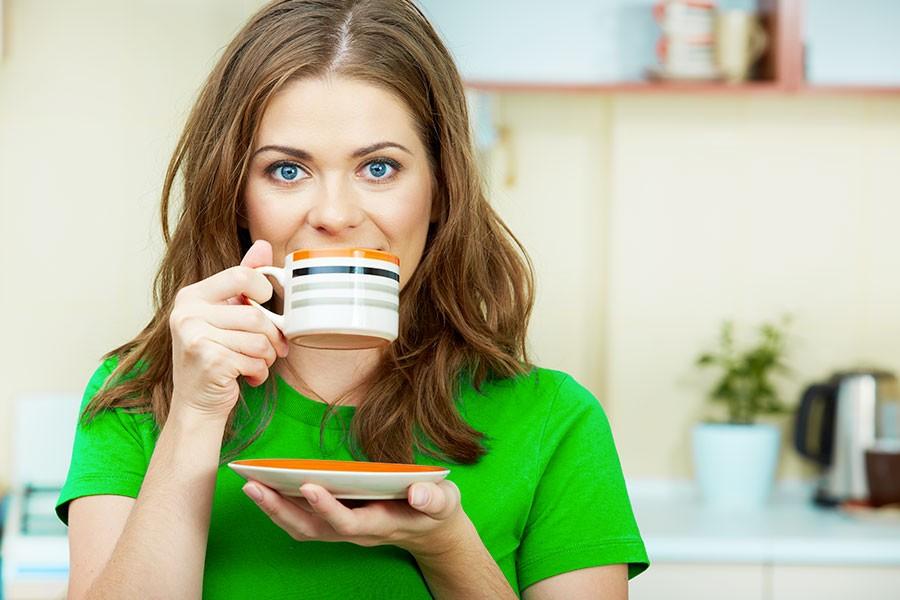 Ragazza beve una tazza di caffè verde