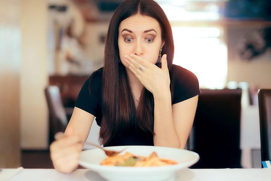 donna con attacco di gastrite a tavola
