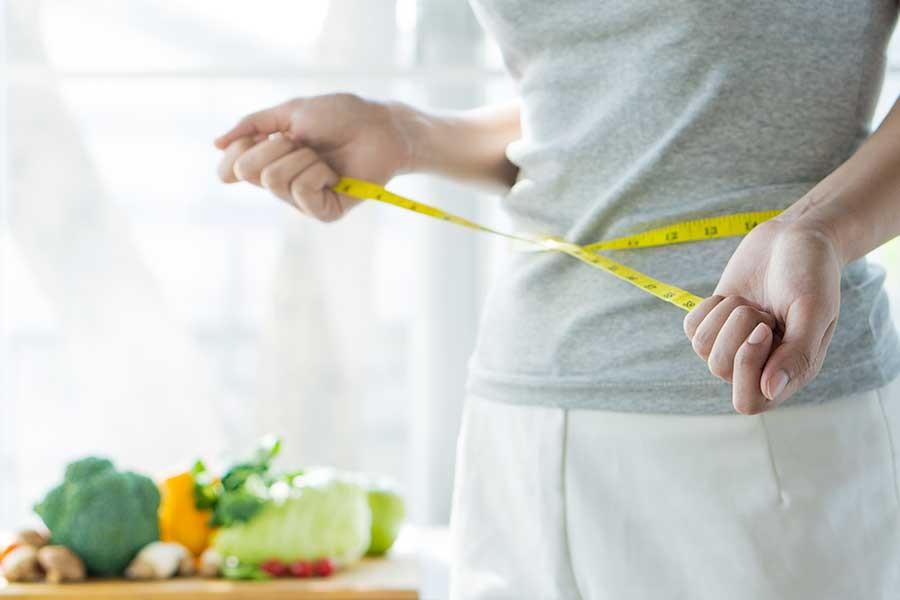 giovane donna misura il proprio girovita