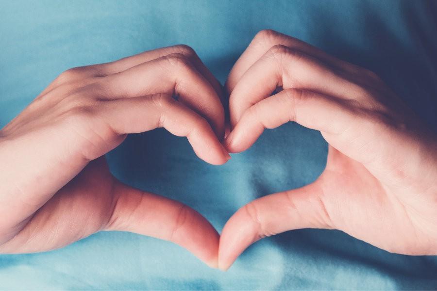 Donna in salute fa un cuore con le mani sul suo stomaco