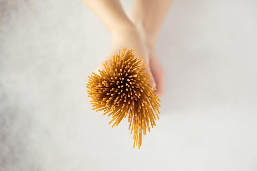 Donna tiene in mano un mucchio di spaghetti integrali per la sua dieta bilanciata