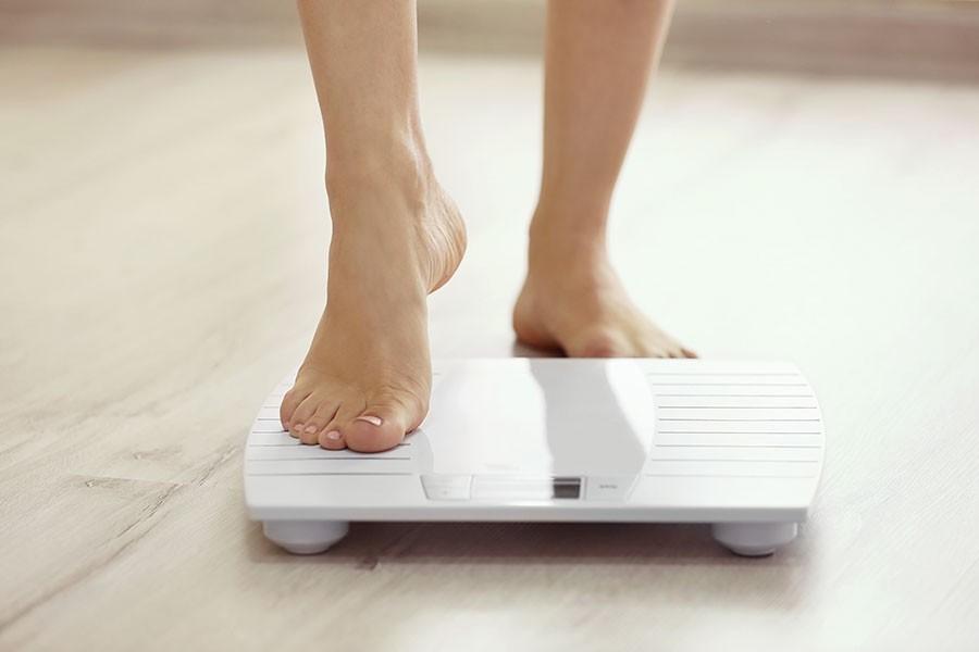 donna si pesa sulla bilancia