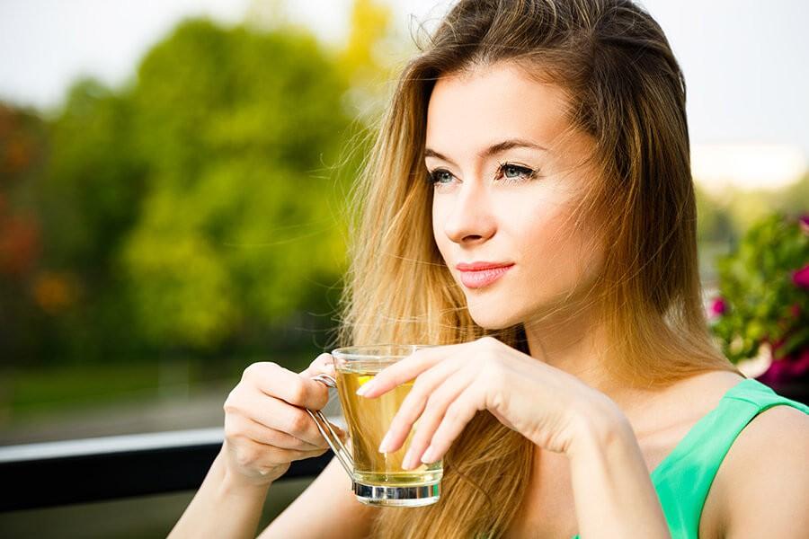 Ragazza sorseggia una tazza di te verde utile contro la ritenzione idrica