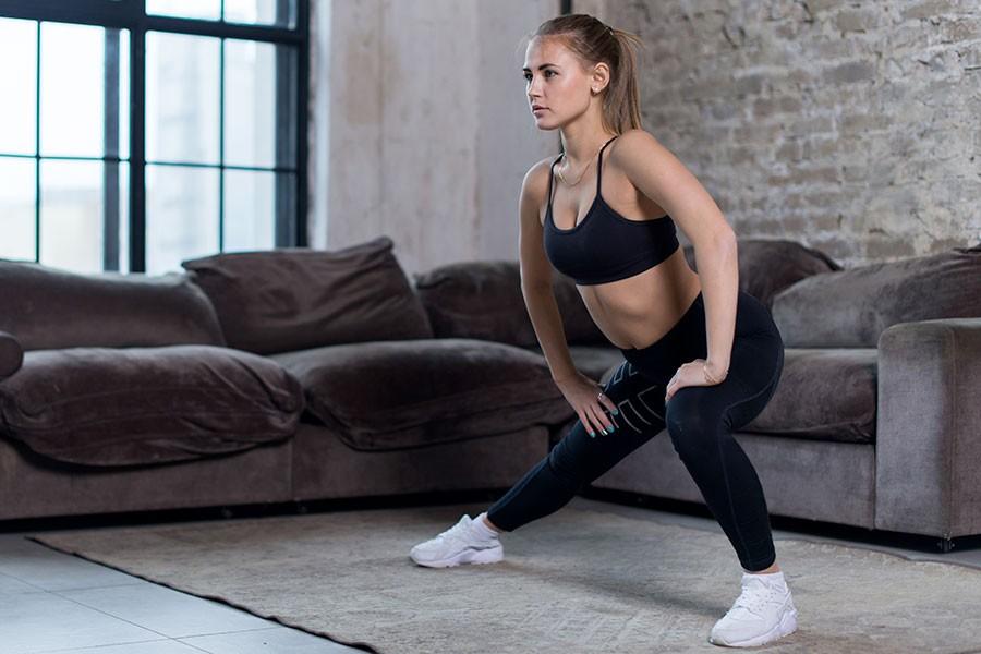 Ragazza riscalda i muscoli prima della sessione di home fitness