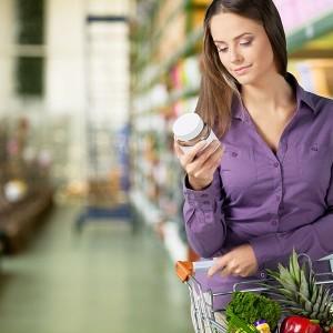 ragazza al supermarket legge un'etichetta alimentare