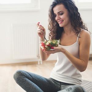 Una giovane ragazza mangia un'insalata
